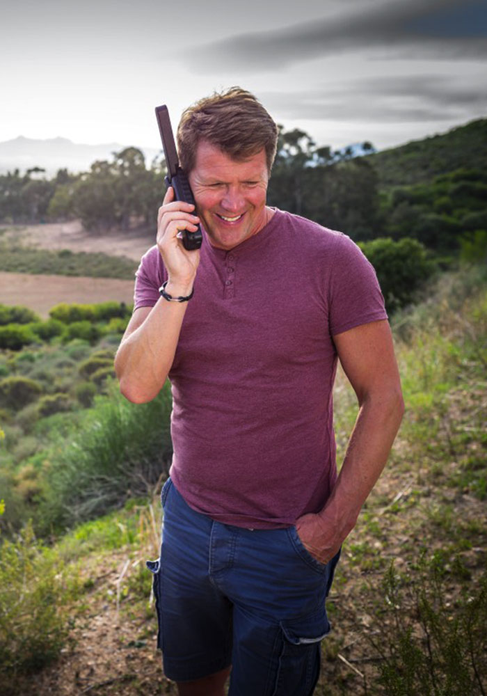 Guy happily using a satellite phone