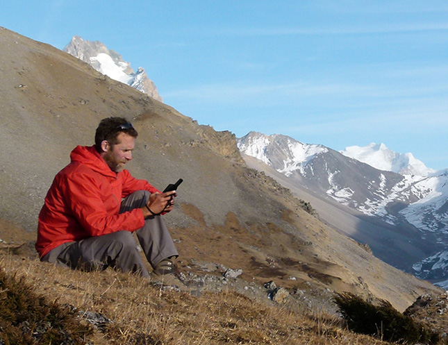 Guy on a hill with a satellite phone